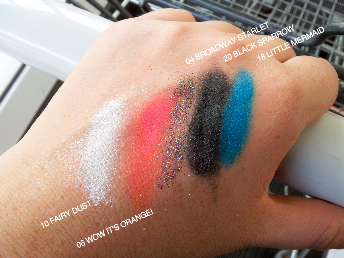 Ein Foto von unterwegs: Swatches der essence-Pigmente 10 fairy dust, 06 wow it's orange!, 04 broadway starlet, 20 black sparrow , 18 little mermaid